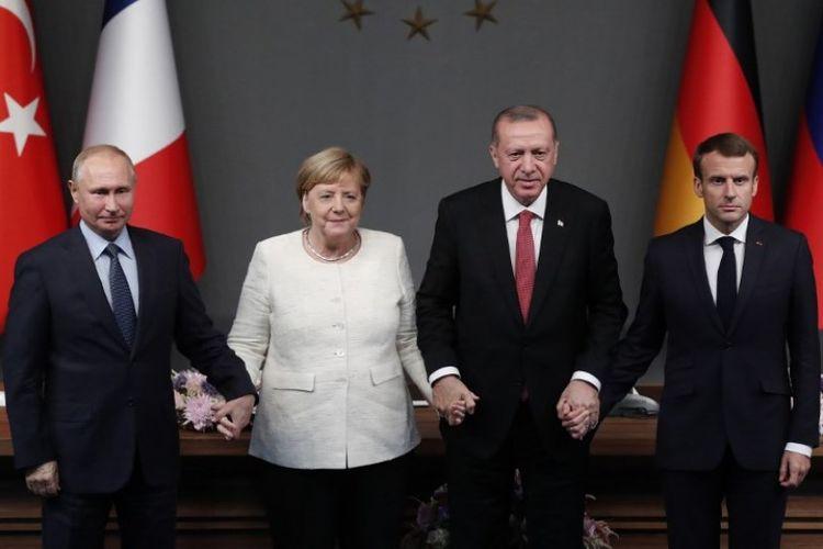 (Dari kiri ke kanan) Presiden Rusia Vladimir Putin, Kanselir Jerman Angela Merkel, Presiden Turki Recep Tayyip Erdogan dan Presiden Prancis Emmanuel Macron berpegangan tangan setelah konferensi pers dalam pertemuan mencari solusi politik abadi terhadap perang saudara di Suriah. Pertemuan digelar di Vahdettin Mansion di Istanbul, pada Sabtu (27/10/2018). (AFP/Maxim Shipenkov)