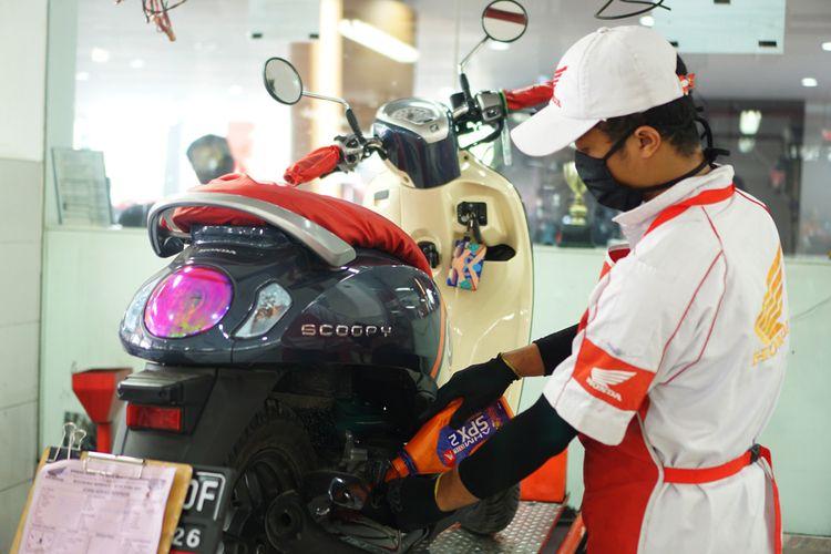 Ilustrasi perawatan motor dengan ganti oli mesin di bengkel resmi AHASS