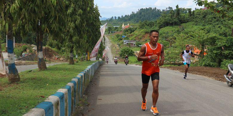 Peserta Aquathlon Raja Ampat 2017 berlari menaiki jalanan berbukit di Waisai, Kabupaten Raja Ampat, Papua Barat, Sabtu (21/10/2017). Sebanyak 320an peserta mengikuti Aquathlon pertama yang menempuh 600 meter dengan berenang, dan enam kilometer berlari marathon mengelilingi kota Waisai dalam Festival Bahari Raja Ampat 2017.