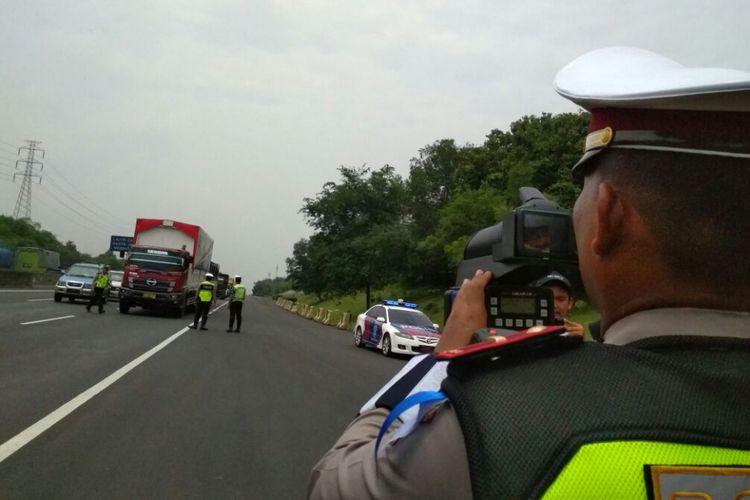 Polisi menggunakan alat speed gun untuk mengukur kecepatan kendaraan di Tol Jakarta-Cikampek dalam penutupan Operasi Zebra Lodaya 2017, Selasa (14/11/2017).