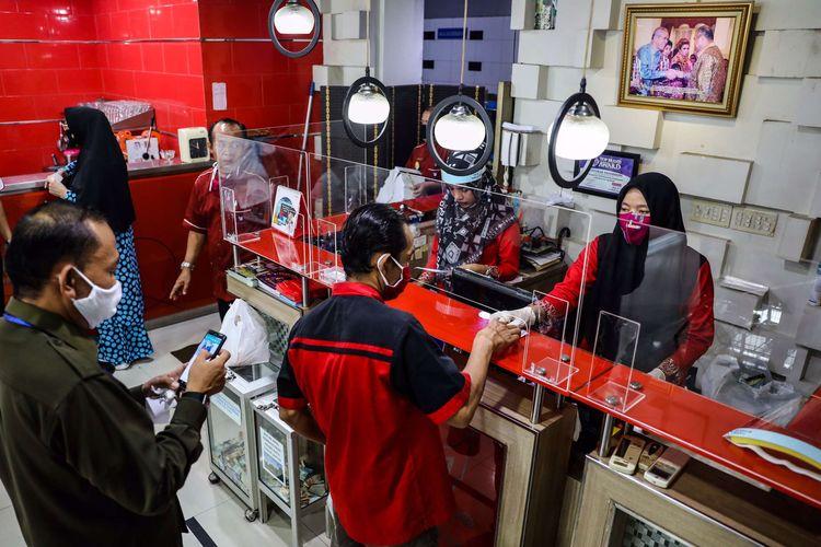 Pelayan menggunakan masker dan pelindung wajah saat melayani pengunjung di kasir di Restoran Sederhana, Bendungan Hilir, Jakarta Pusat, Senin (8/6/2020). Sebagai bagian dari rencana penerapan kenormalan baru 8 Juni 2020, pemerintah DKI Jakarta mengharuskan pengusaha rumah makan membatasi kapasitas maksimal 50 persen, larangan penyajian makanan secara prasmanan dan tetap menerapkan protokol kesehatan.