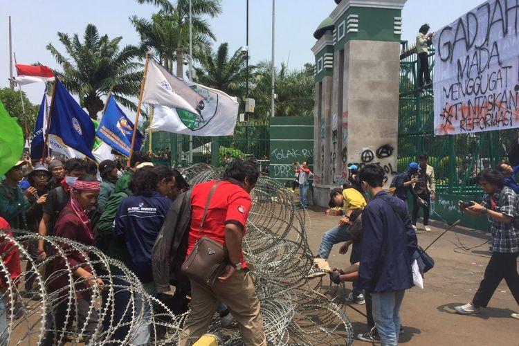 Massa mahasiswa merusak barier kawat berduri di depan Gedung DPR RI, Jalan Gatot Subroto, Jakarta Pusat, Selasa (24/9/2019).