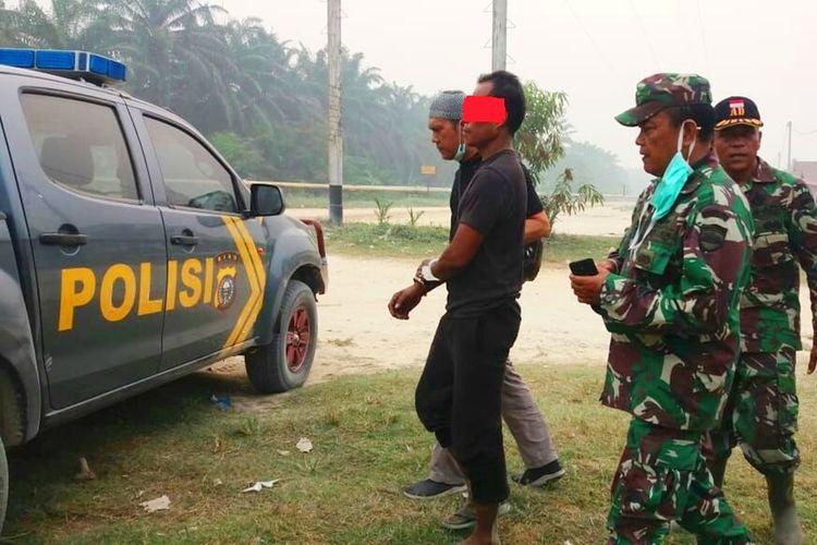 Petugas kepolisian dan TNI saat mengamankan seorang pelaku karhutla di Kecamatan Bonai Darussalam, Kabupaten Rohul, Riau, Sabtu (21/9/2019).