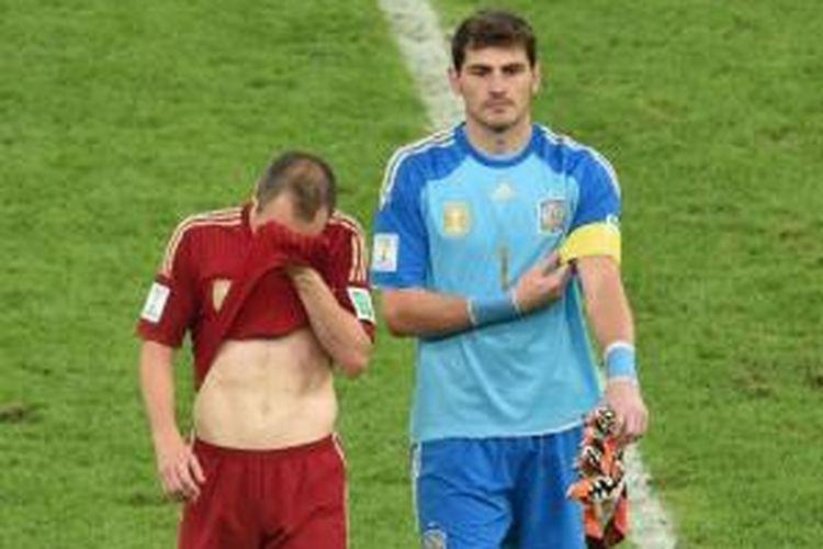 Kiper Spanyol Iker Casillas (kanan) dan pemain gelandang Andres Iniesta berjalan dengan lesu saat timnya dikalahkan 0-2 oleh Cile di Stadion Maracana, Rio de Janeiro, Rabu (18/6/2014).