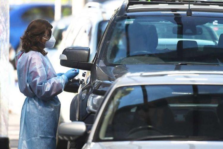 Petugas kesehatan bertugas di layananan pengetesan Covid-19 drive-thru di Keilor, Melbourne, Rabu, 1 Juli 2020.