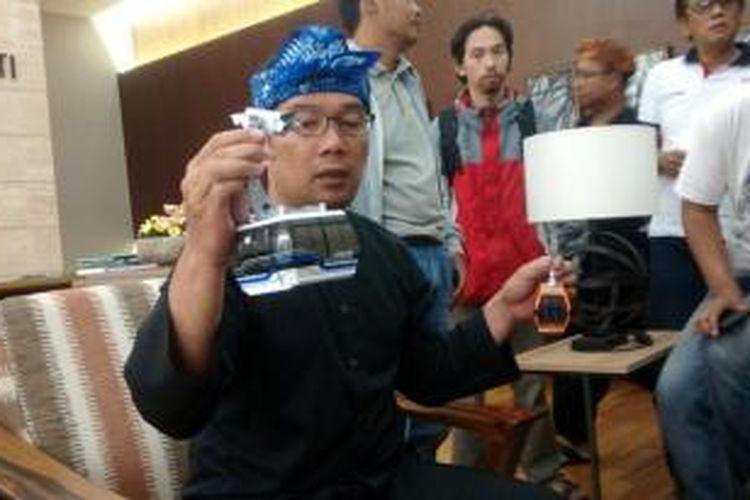 Wali Kota Bandung, Ridwan Kamil, menunjukkan miniatur contoh cable car yang akan dipasang di Kota Bandung. Cable car dari Austria ini memiliki kapasitas 36 orang.