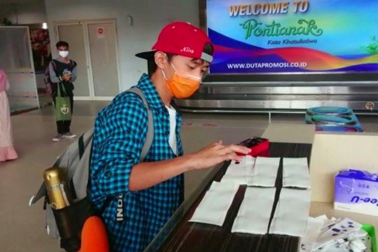 Seorang warga yang baru tiba melalui Bandara Supadio Pontianak, Kalbar, diminta mencelupkan semua jarinya ke tinta biru yang disediakan. Selain itu, warga tersebut otomatis jadi orang dalam pemantauan (ODP).