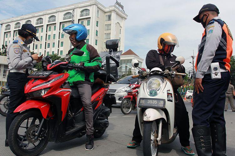 Petugas Dishub Jakarta memeriksa surat kelengkapan kendaraan dan juga surat izin keluar masuk (SIKM) Jakarta saat razia plat nomor kendaraan luar Jakarta di Jalan Ciledug Raya, Jakarta, Rabu (27/5/2020). Pengendara yang tidak memiliki SIKM Jakarta kemudian diputar balik agar tidak memasuki wilayah Ibu Kota.