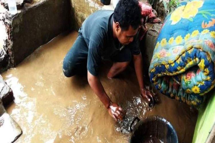 Warga korban banjir saat membersihkan sisa-sisa air dan lumpur yang masuk ke dalam rumah.