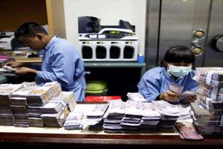Petugas menyortir uang pecahan Rp. 10.000 di Sentra Operasi Kas (SOK) di kantor BRI Pusat di Jakarta, Rabu (28/3/2012).