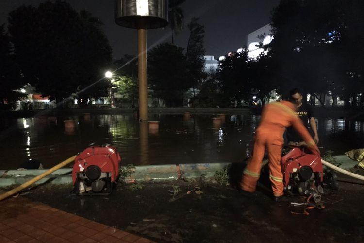 Petugas pemadam kebakaran menyedot air dari Kolam Taman Martha Tiahahu, Kebayoran Baru, Jakarta pada Sabtu (22/8/2020) malam untuk menyuplai air dan digunakan untuk memadamkan api yang membakar gedung Kejaksaan Agung.
