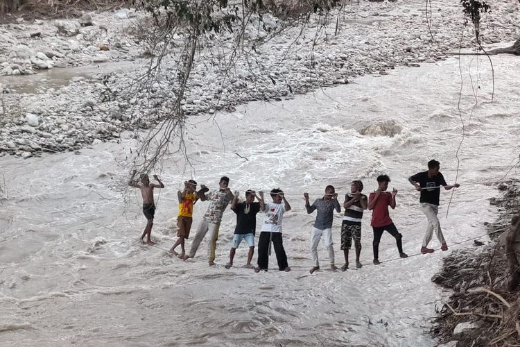 Warga Malaka sedang melintasi sungai melalui bekas kabel listrik