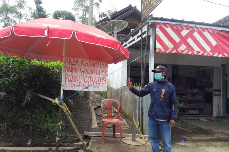 Seorang Satgas Covid-19 Desa Cigedug, Garut, Jawa Barat, menjaga salahsatu pintu masuk ke kampung yang diisolasi mandiri, Selasa (22/04/2020)