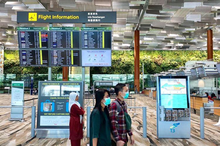 Pasangan muda-mudi terlihat memakai masker di Terminal 3 Bandara Internasional Changi di tengah mewabahnya virus corona di Singapura.