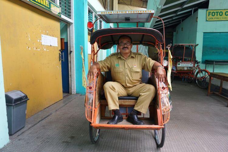 Guru Teknik Listrik SMK Piri I Yogyakarta, Raden Sunarto saat berada di atas becak listrik tenaga Surya buatannya.