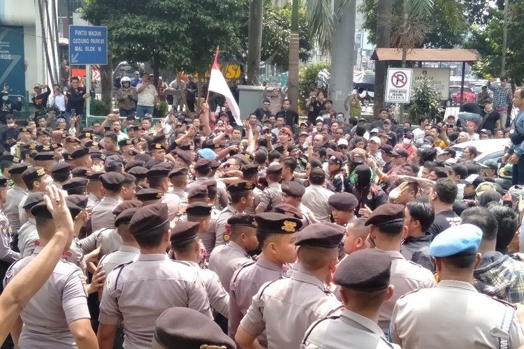 Massa aksi mencoba masuk ke dalam kantor Gojek. Massa dan polisi sempat melakukan aksi saling dorong di depan kantor Gojek, Senin (5/8/2019).