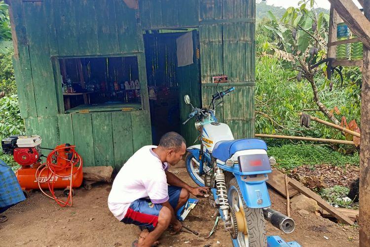 Foto :Stefanus Sai (33),penyandang disabilitas asal Kampung Ketang, Desa Golo Tolang, Kecamatan Kota Komba, Kabupaten Manggarai Timur, NTT, sedang mengecek kerusakan motor pelanggan, Minggu (12/7/2020).