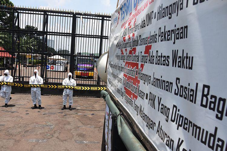 Polisi mengenakan masker dan pakaian hazmat saat mengamankan unjuk rasa penolakan buruh terhadap Omnibus Law Rancangan Undang-Undangan (RUU) Cipta Kerja di depan kompleks Parlemen, Jakarta, Rabu (30/9/2020). Penggunaan pakaian pelindung diri tersebut dilakukan sebagai antisipasi polisi terhadap penularan Covid-19 selama pengamanan terhadap pengunjuk rasa.
