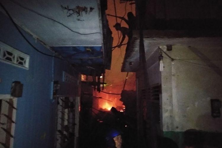 Seorang petugas pemadam kebakaran menghancurkan bagian rumah yang terbakar untuk mengantisipasi menjalarnya kobaran api, Selasa malam (1/10/2019). Di lokasi ini, diperkirakan puluhan rumah musnah dilahap si jago merah.