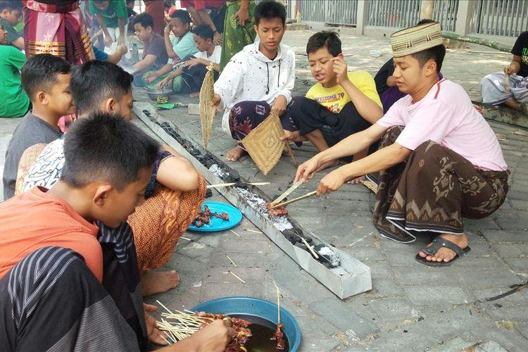 Para santri di Pondok Pesantren Tebuireng Jombang Jawa Timur, membakar sate dari daging hewan kurban yang diterima dari panitia penyembelihan kurban di lingkungan Pondok, Minggu (11/8/2019).