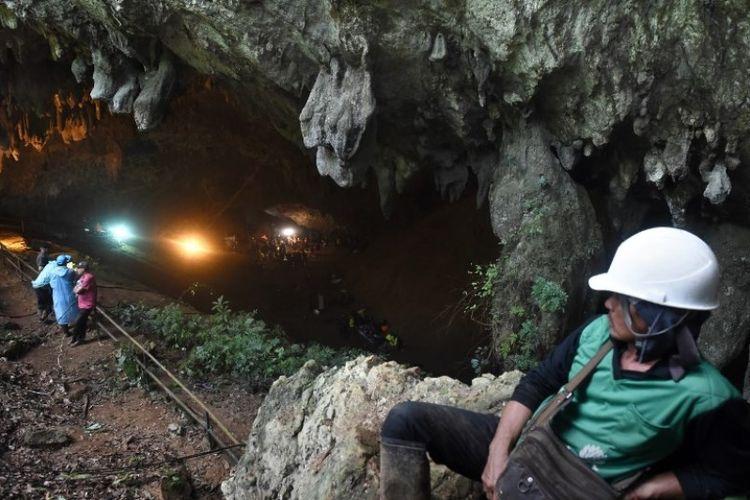 Tim penyelamat terlihat di depan gua Tham Luang di Taman Hutan Non Khun Nam Nang di Chiang Rai, Tabu (27/6/2018). Mereka berupaya menyelamatkan 12 remaja dan pelatih mereka yang hilang selama beberapa hari di dalam gua. (AFP/Lillian Suwanrumpha)