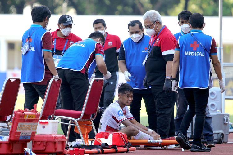 Pemain Madura United Moch Kevy Syahertian mendapat perawatan seusai mengalami benturan keras dengan kepala pemain PS Sleman Mario Maslac pada pekan keempat yang berakhir dengan skor 1-0 di Stadion Madya Jakarta, Sabtu (25/9/2021) malam.
