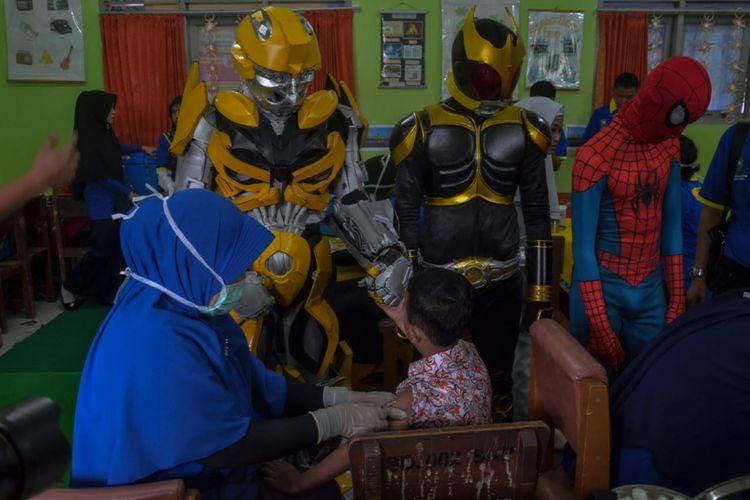 Siswa SDN 02 Pekanbaru, Riau, menjalani imunisasi campak dan Rubella yang ditemani satria baja hitam, spiderman dan robot, Rabu (1/8/2018).