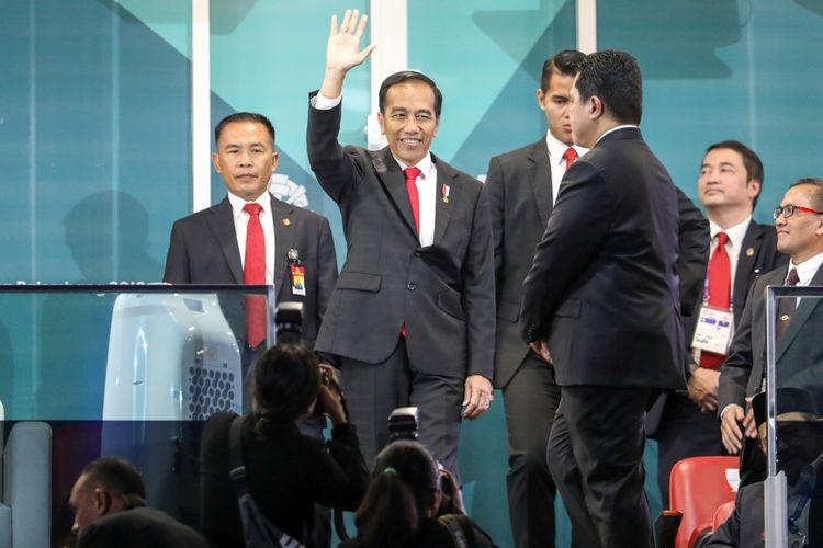 Presiden Joko Widodo melambaikan tangan ke arah penonton saat  pembukaan Asian Games 2018  di Stadion Utama Gelora Bung Karno , Senayan, Jakarta, Sabtu (18/8/2018).