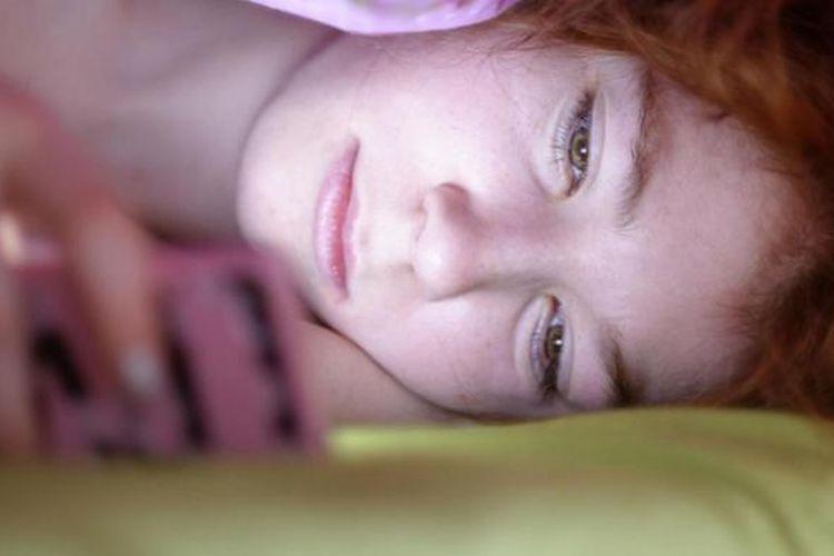Ilustrasi: Melihat layar ponsel sambil tidur.