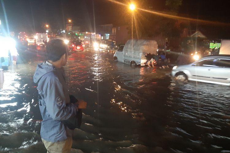 Warga sekitar bantu mendorong mobil yang terjebak banjir di sekitar pabrik Kahatex, Cimanggung, Sumedang, Jawa Barat, Rabu (29/1/2020). AAM AMINULLAH/KOMPAS.com