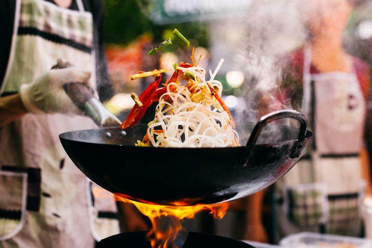 Ilustrasi orang masak mi menggunakan wok.