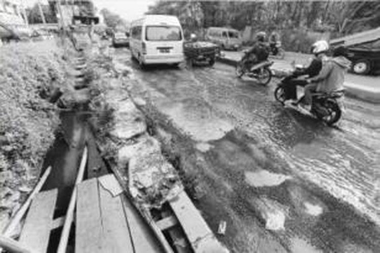 Pengendara kendaraan bermotor harus berhati-hati melewati Jalan RE Martadinata, Pamulang, Tangerang Selatan, yang rusak parah. Tidak hanya jalan, trotoar pun rusak parah dan tidak bisa dilalui pejalan kaki.