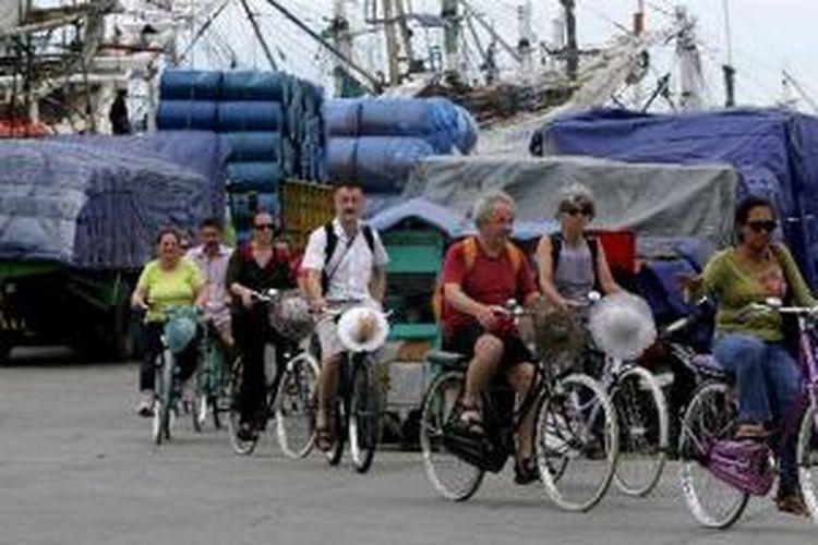 Rombongan turis mancanegara menggunakan sepeda sewaan berkeliling di kawasan Pelabuhan Sunda Kelapa, Jakarta, Rabu (30/3/2011). Wisata kota tua dengan mengunjungi situs bangunan tua dan lokasi bersejarah merupakan salah satu paket yang digemari turis mancanegara yang berkunjung ke Jakarta.
