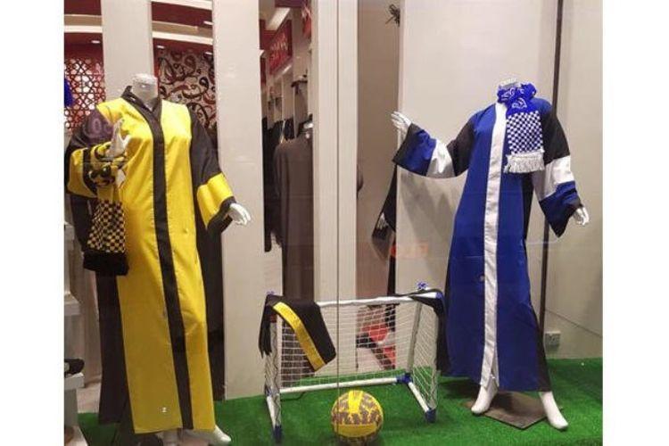 Foto di sebuah toko Arab Saudi yang memajang abaya khusus tim Saudi Pro League. Yakni Al-Ittihad Jeddah (kiri), dan Al-Hilal Riyadh (kanan). Abaya ini dijual setelah otoritas Saudi mengizinkan perempuan masuk ke stadion untuk menonton pertandingan sepak bola