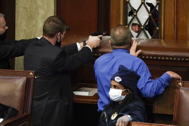 Lihat Foto Polisi dengan senjata ditarik berjaga-jaga ketika pengunjuk rasa mencoba masuk ke Ruang DPR di Capitol AS pada hari Rabu, 6 Januari 2021, di Washington.(AP PHOTO/ J SCOTT APPLEWHITE)