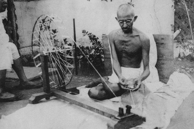Mahatma Gandhi sedang memintal kain. Foto ini diambil pada tahun 1920-an.
