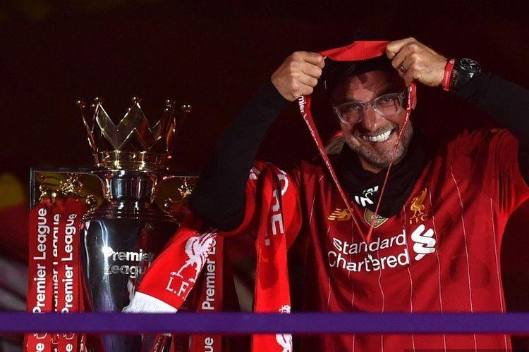Pelatih Liverpool, Jurgen Klopp, melewati trofi Liga Inggris sambil mengalungkan medali juara di Stadion Anfield, Rabu 22 Juli 2020. Penyerahan trofi juara Premier League ini dilakukan seusai laga Liverpool vs Chelsea dalam lanjutan pekan ke-37 Liga Inggris.