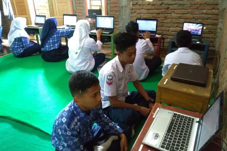 Peserta UNBK Madrasah Ibtidaiyah dan Madrasah Tsanawiyah Salu Bua, kecamatan Suli Barat, kabupaten Luwu, Sulawesi Selatan, mengikuti UNBK di rumah warga untuk mendapatkan jaringan internet, Kamis (25/04/2019)