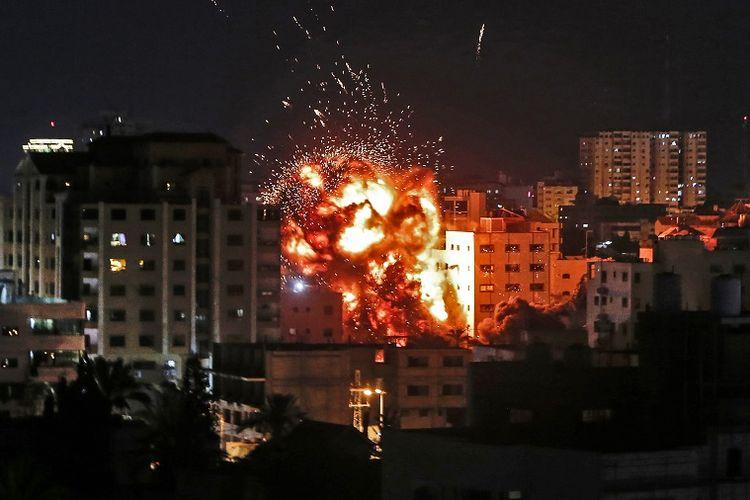 Ledakan terlihat di antara bangunan selama serangan udara Israel di Kota Gaza pada Sabtu (4/5/2019). (AFP/Mahmud Hams)