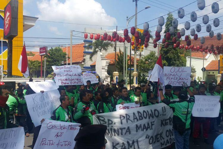 DEMO--Ratusan ojek online menggelar demonstrasi di depan Kantor Walikota Madiun menuntut calon presiden Prabowo Subianto meminta maaf lantaran menghina profesi mereka sebagai ojek online, Selasa ( 27/11/2018) pagi.