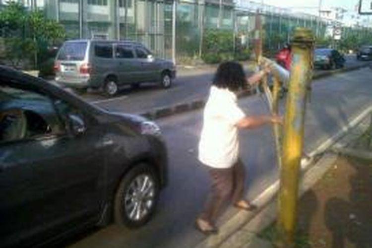 Seorang wanita turun dari mobil Suzuki Ertiga B 1497 TZW dan membuka portal Busway di Koridor XI jurusan Kampung Melayu-Walikota Jakarta Timur, Kamis (1/8/2013). Wanita tersebut bahkan sempat meneriaki petugas.