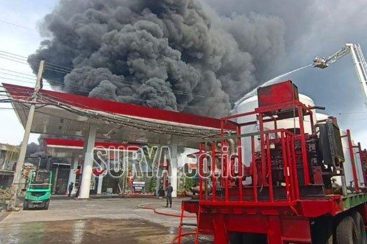 Asap hitam tebal yang membumbung akibat kebakaran pabrik palet plastik yang letaknya berdempetan dengan SPBU Margomulyo Kota Surabaya, Rabu (31/3/2021).