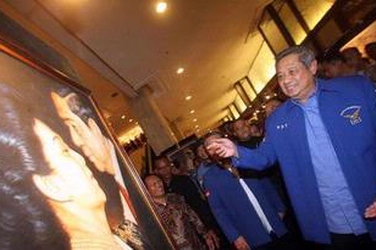 Ketua Majelis Tinggi Partai Demokrat Susilo Bambang (kanan) Yudhoyono melihat lukisan dirinya bersama Ibu Ani Yudhoyono usai memberikan keterangan pada wartawan dalam konferensi pers Rapat Pimpinan Nasional PD, di Hotel Sahid, Jakarta, Minggu (17/2/2013).