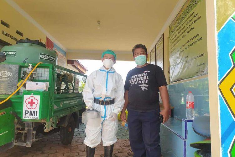 RELAWAN TERMUDA-- Fitra Adi Wibowo (18) (kiri) menjadi relawan termuda yang masuk dalam tim pemakaman pasien covid-19 di Kota Madiun, Jawa Timur. Semenjak bergabung dengan tim tahun lalu, Fitra setidaknya sudah memakamkan 200-an jenazah pasien kasus covid-19 di kota pendekar.