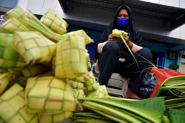 Seorang pedagang mengenakan masker saat menjual sarang ketupat untuk persiapan Hari Raya Idul Adha 1442 Hijriyah di Pasar Batu Merah, Kota Ambon, Maluku, Minggu (18/7/2021). Sejumlah pedagang menyatakan permintaan sarang ketupat tetap ramai idul Adha, di tengah pelaksanaan Pemberlakuan Pembatasan Kegiatan Masyarakat (PPKM) Mikro di Ambon, dan pedagang menjual ketupat berkisar Rp7.000-Rp10.000 per ikat isi 10 ketupat. ANTARA FOTO/FB Anggoro/foc.