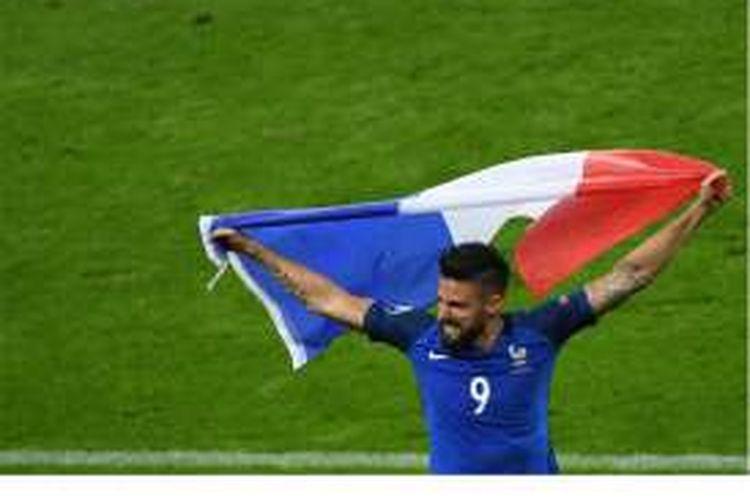 Penyerang Perancis, Olivier Giroud, memegang bendera Perancis usai timnya menang 5-2 atas Islandia pada perempat final Piala Eropa 2016 di Stade de France, Saint-Denis, Minggu (3/7/2016).