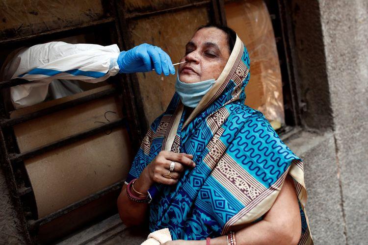 Seorang tenaga medis mengambil sampel dari seorang perempuan di sebuah sekolah yang diubah menjadi tempat untuk melakukan tes penyakit virus korona (COVID-19) di tengah penyebaran penyakit tersebut di New Delhi, India, Senin (22/6/2020).
