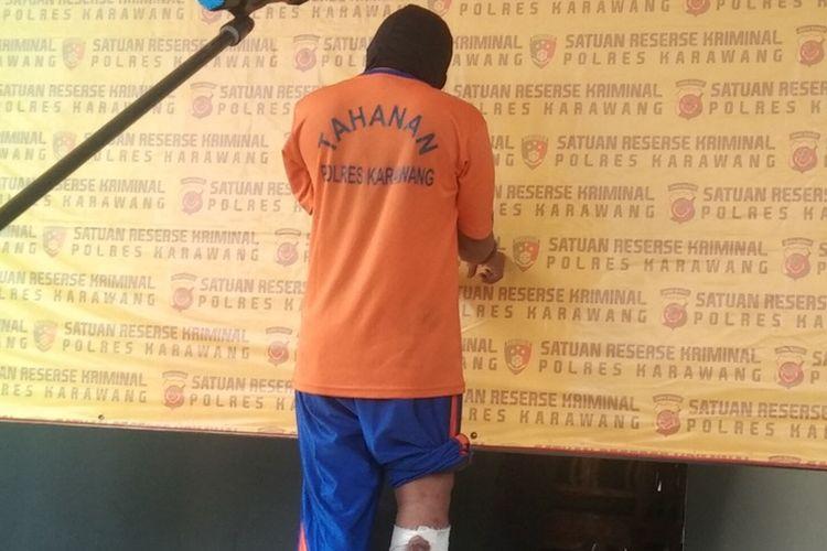 AR, pelaku begal yang sempat beraksi di Lingkar Luar Karawang dan kini ditangkap, saat press release di Mapolres Karawang, Senin (30/8/2021).