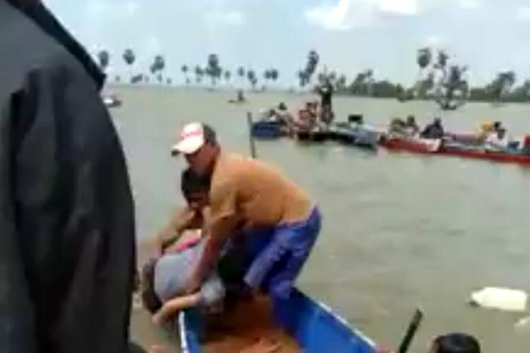 Seorang korban dievakuasi ke perahu oleh nelayan setelah 2 jam pencarian di danau Tempe, Kabupaten Soppeng, Sulawesi Selatan. Minggu, (26/7/2020).