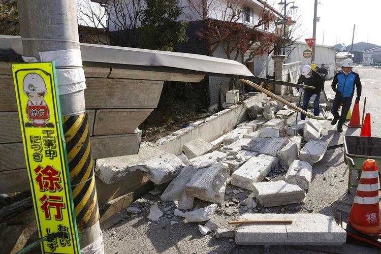 Penduduk di timur laut Jepang pada Minggu membersihkan kekacauan di toko dan rumah setelah gempa bumi pada Sabtu (13/2/2021).